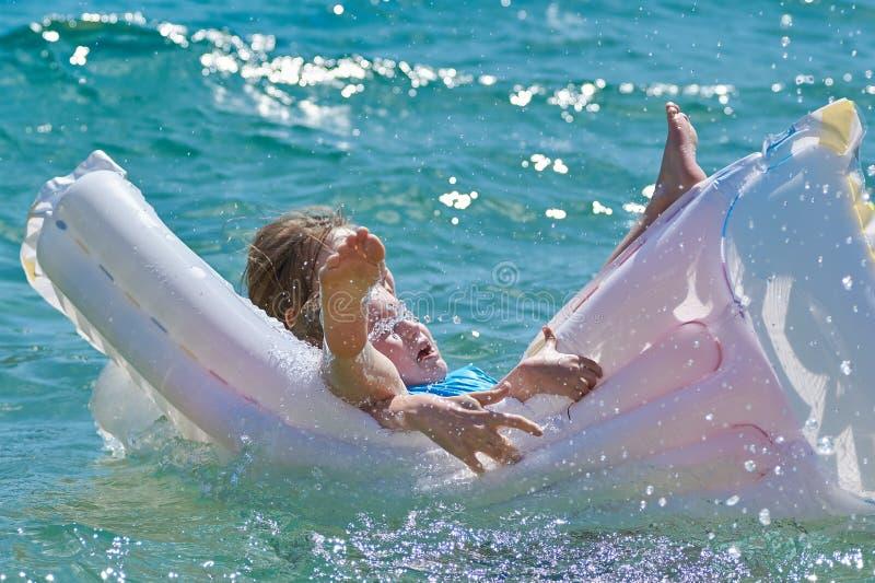 Glückliche Kinder, die mit Matratze in Meer spielen stockbild