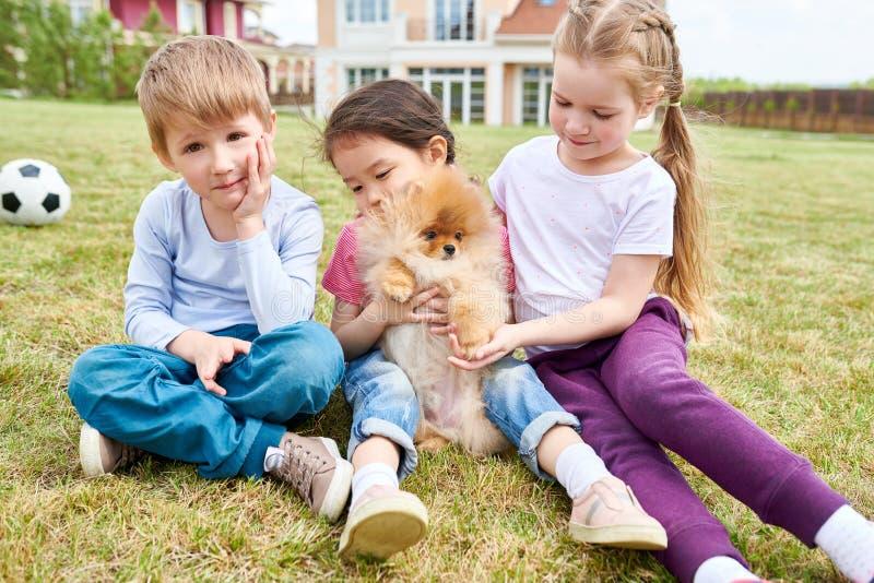Glückliche Kinder, die mit nettem Welpen spielen lizenzfreies stockbild