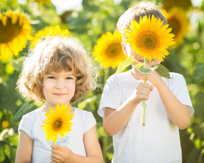 Glückliche Kinder, die mit Sonnenblumen spielen stockbild