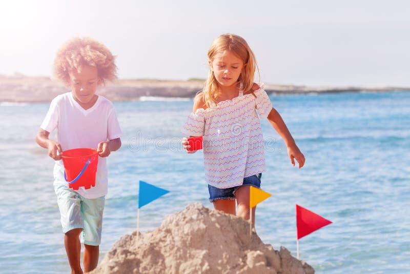 Glückliche Kinder, die Sandburg an der Küste machen lizenzfreies stockfoto