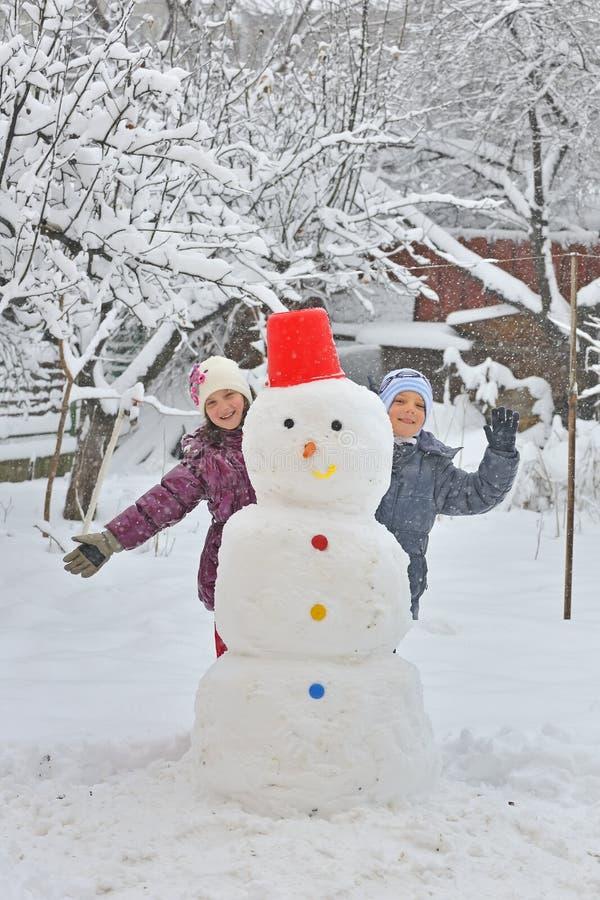 Glückliche Kinder, die Schneemann errichten stockfotos