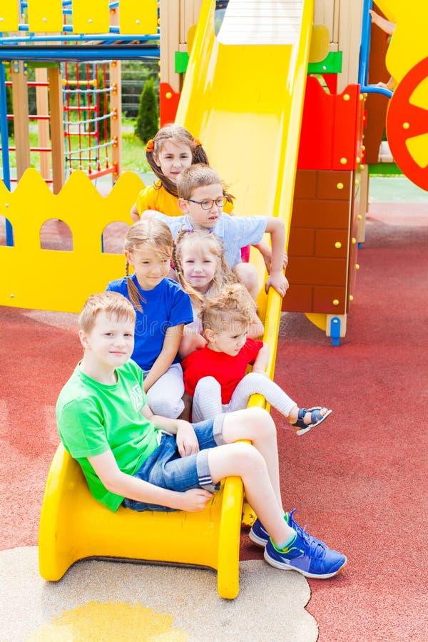 Glückliche Kinder, die am Spielplatz spielen lizenzfreies stockfoto
