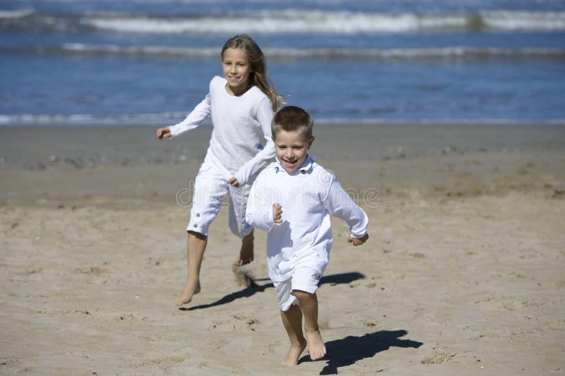 Glückliche Kinder, die am Strand spielen lizenzfreies stockfoto