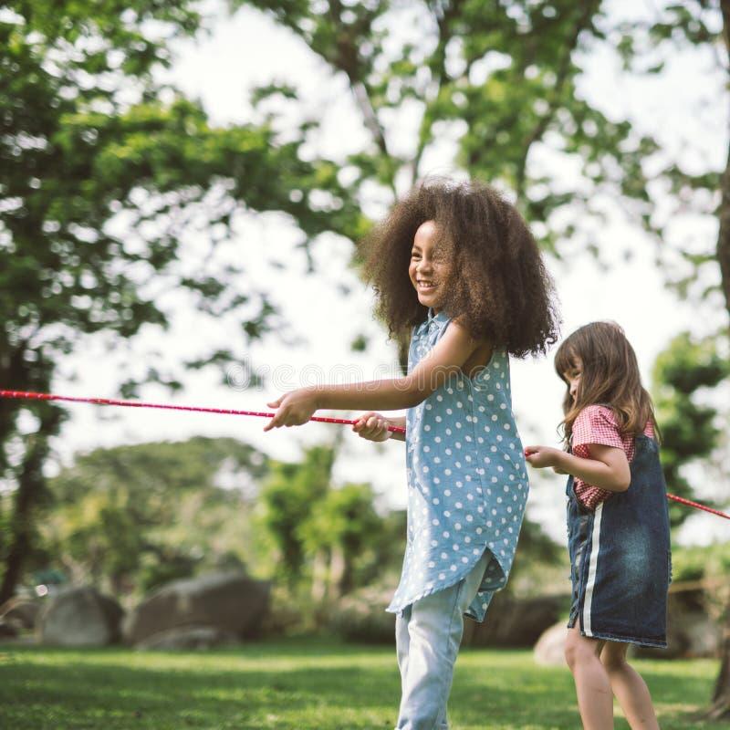 Glückliche Kinder, die Tauziehen spielen lizenzfreie stockfotos