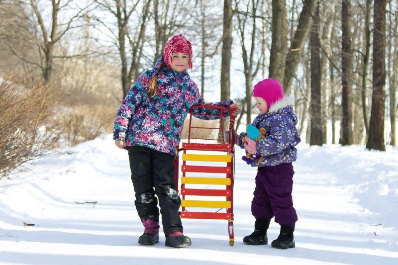 Glückliche Kinder, die zusammen auf einem Gehweg in einem Park des verschneiten Winters eine Holding die Schlitten stehen stockbild