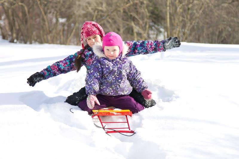 Glückliche Kinder, die zusammen auf einem Schlitten in einer Schneewehe an einem klaren Wintertag sitzen stockfotografie