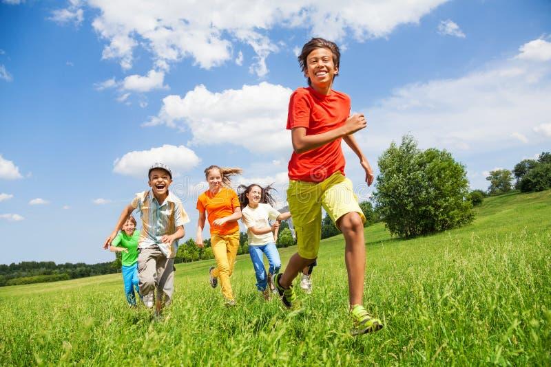 Glückliche Kinder, die zusammen in das Feld laufen stockbild