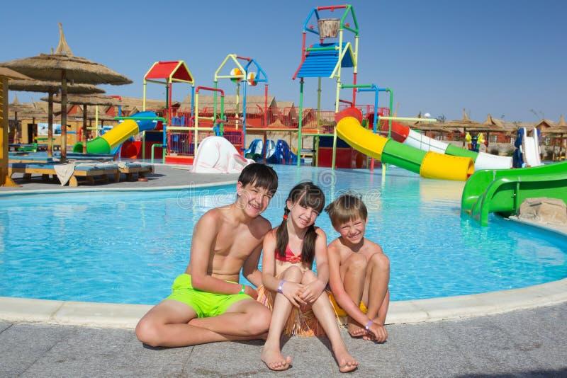 Glückliche Kinder durch Pool stockfoto