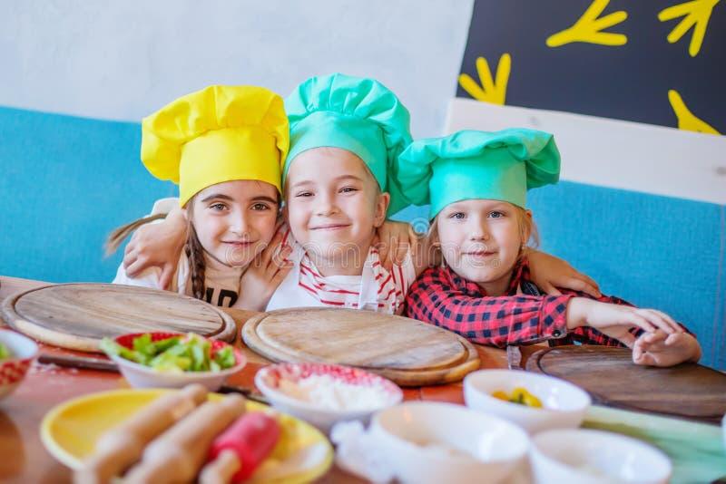 Glückliche Kinder an einem Pizzakochen lizenzfreies stockfoto