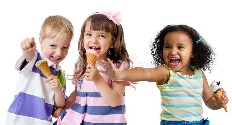 Glückliche Kinder gruppieren das Essen der Eiscreme, die auf Weiß lokalisiert wird stockfoto