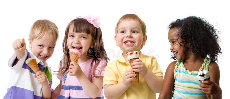 Glückliche Kinder gruppieren das Essen der Eiscreme, die auf Weiß lokalisiert wird lizenzfreie stockbilder