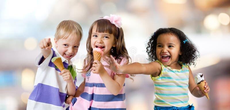 Glückliche Kinder gruppieren das Essen der Eiscreme an einer Partei lizenzfreies stockbild