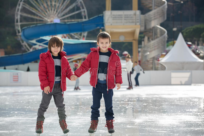 Glückliche Kinder, Jungen, Brüder mit den roten Jacken, laufend während eis stockbilder