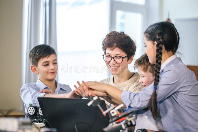 Glückliche Kinder lernen die Programmierung unter Verwendung der Laptops auf extrakurrikularen Klassen lizenzfreie stockfotografie