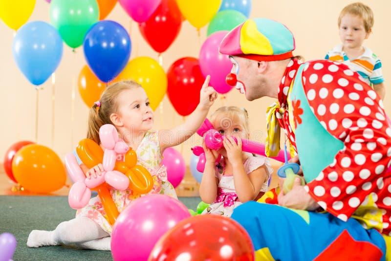 Glückliche Kinder mit Clown auf Geburtstagsfeier stockfotos