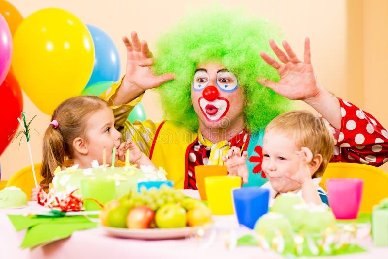 Glückliche Kinder mit Clown auf Geburtstagsfeier stockfotografie