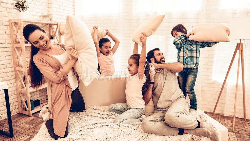 Glückliche Kinder mit den Eltern, die Kissenschlacht haben lizenzfreie stockfotos