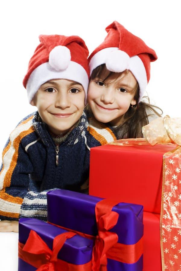 Glückliche Kinder mit Sankt-Hüten mit Weihnachtsgeschenken stockfoto