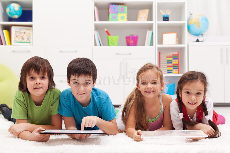 Glückliche Kinder mit Tablettencomputern lizenzfreie stockbilder