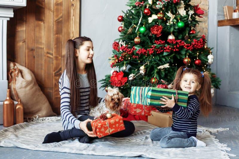 Glückliche Kinder packen Geschenke für Weihnachten aus Das Konzept von Christus lizenzfreie stockfotografie