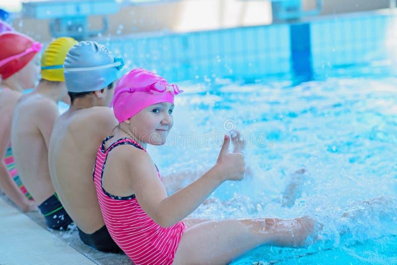 Glückliche Kinder scherzt Gruppe an der Swimmingpoolklasse, die lernt zu schwimmen lizenzfreies stockfoto