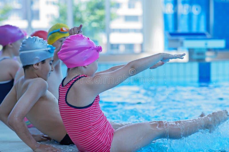 Glückliche Kinder scherzt Gruppe an der Swimmingpoolklasse, die lernt zu schwimmen stockfotos