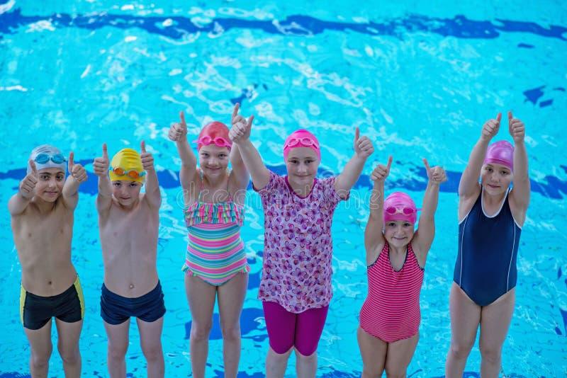 Glückliche Kinder scherzt Gruppe an der Swimmingpoolklasse, die lernt zu schwimmen stockbild