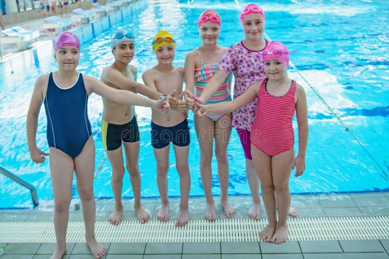 Glückliche Kinder scherzt Gruppe an der Swimmingpoolklasse, die lernt zu schwimmen stockfoto