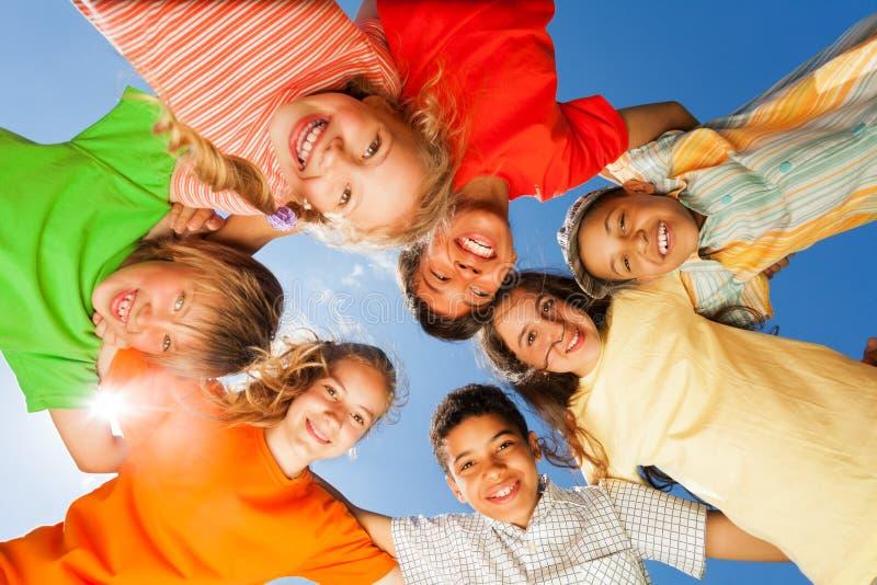 Glückliche Kinder schließen im Kreis auf Himmelhintergrund lizenzfreie stockfotos