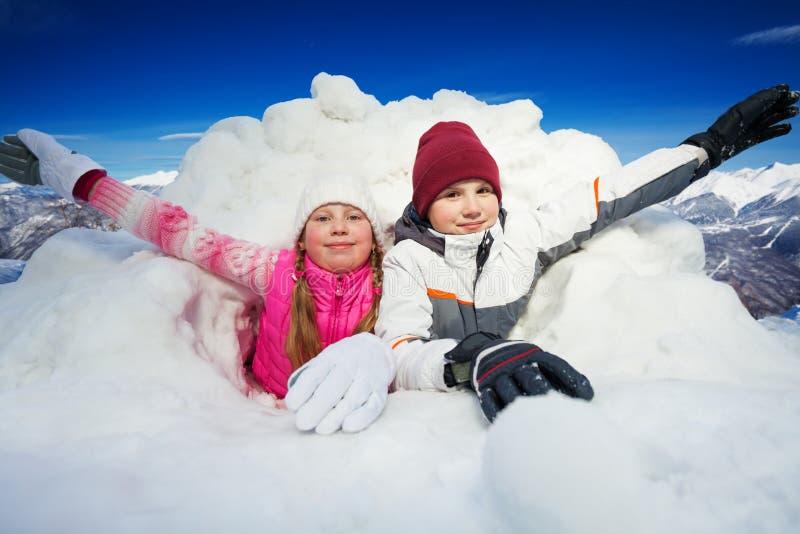 Glückliche Kinder am Schnee höhlen draußen in der Winterzeit aus lizenzfreie stockfotos