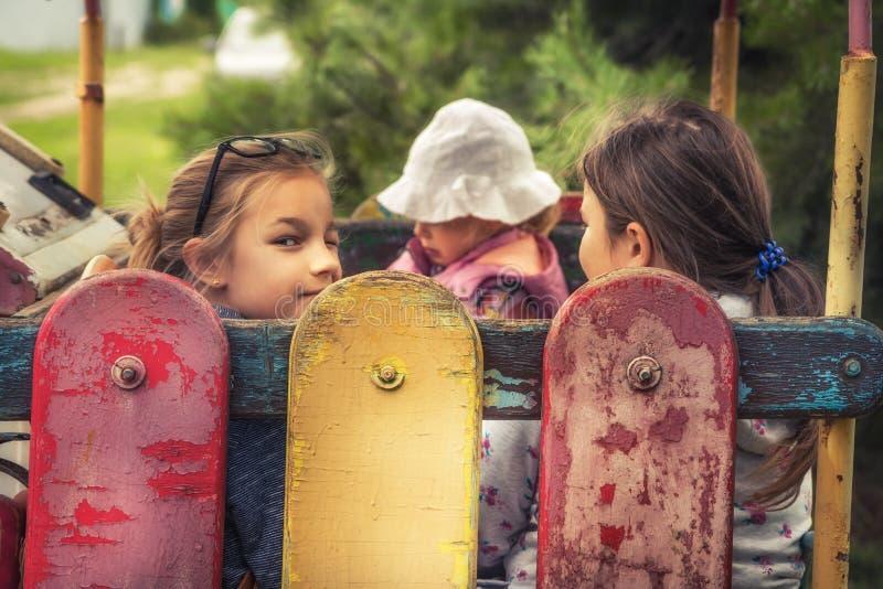 Glückliche Kinder spielen draußen auf Spielplatz Vintage Porträt in der Landschaft symbolisieren glückliche Kindheit stockfotografie