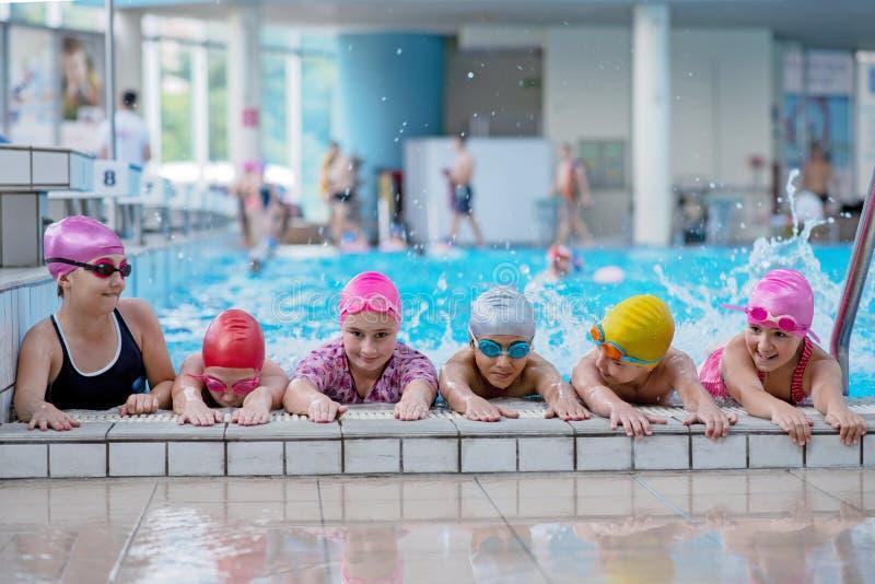 Glückliche Kinder am Swimmingpool Junge und erfolgreiche Schwimmerhaltung stockfotos