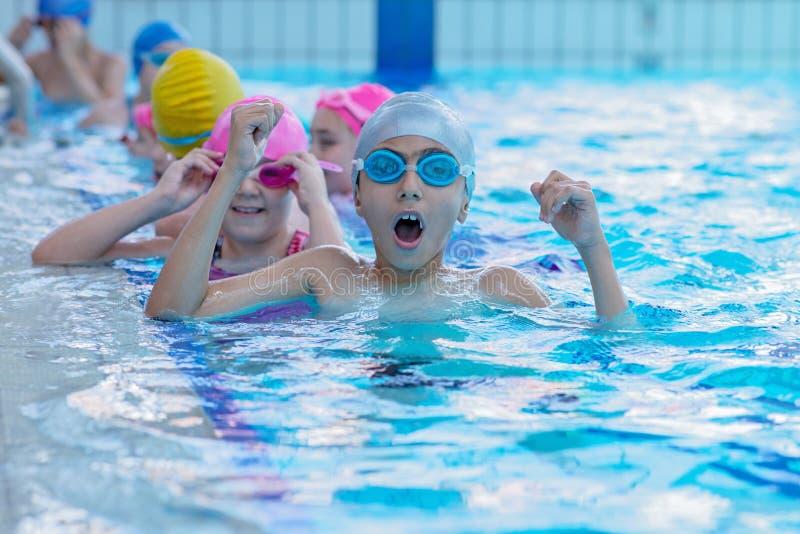 Glückliche Kinder am Swimmingpool Junge und erfolgreiche Schwimmerhaltung lizenzfreie stockfotografie