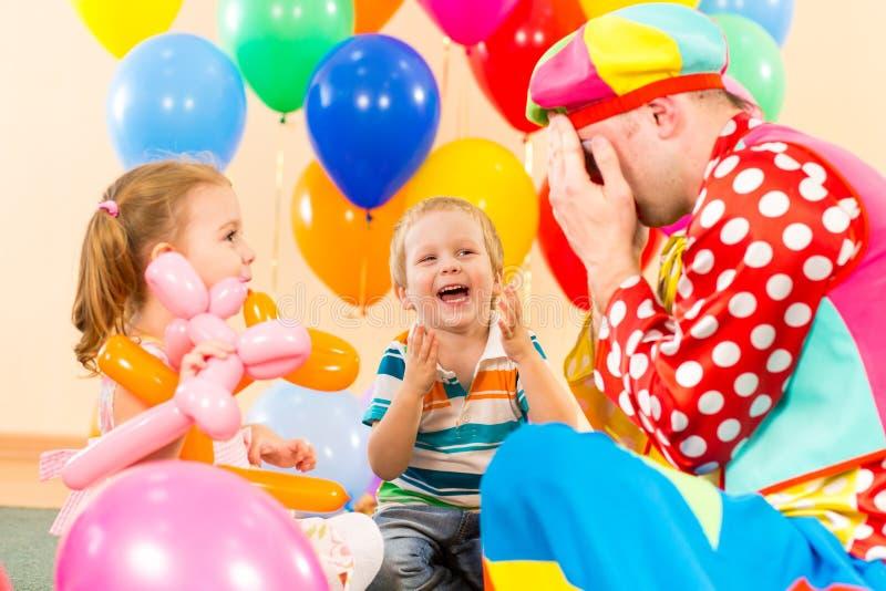 Glückliche Kinder und Clown auf Geburtstagsfeier stockfotos