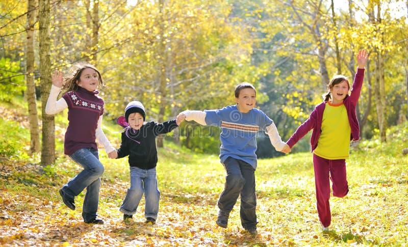 Glückliche Kinder und Herbstlaub lizenzfreies stockfoto