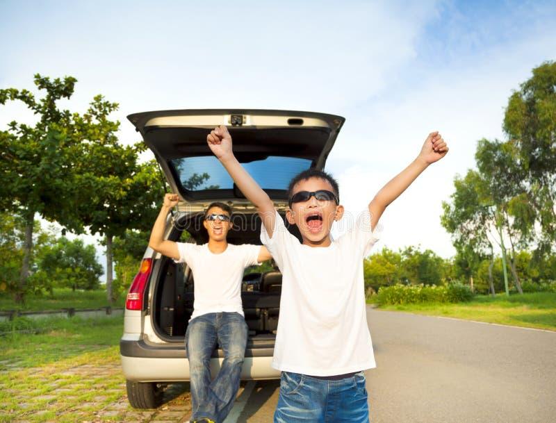 Glückliche Kinder und Vater heben Arme mit ihrem Auto an stockfoto