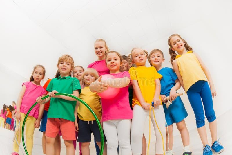 Glückliche Kinder und weibliche Gymnastik trainieren in der Turnhalle lizenzfreie stockbilder