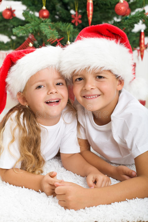 Glückliche Kinder vor Weihnachtsbaum lizenzfreie stockfotografie