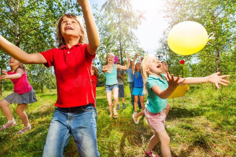 Glückliche Kinder, welche die Ballone im Freien im Sommer spielen stockbilder