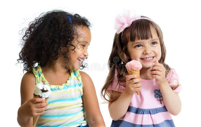 Glückliche Kinder zwei Mädchen, welche die Eiscreme lokalisiert essen stockfotografie