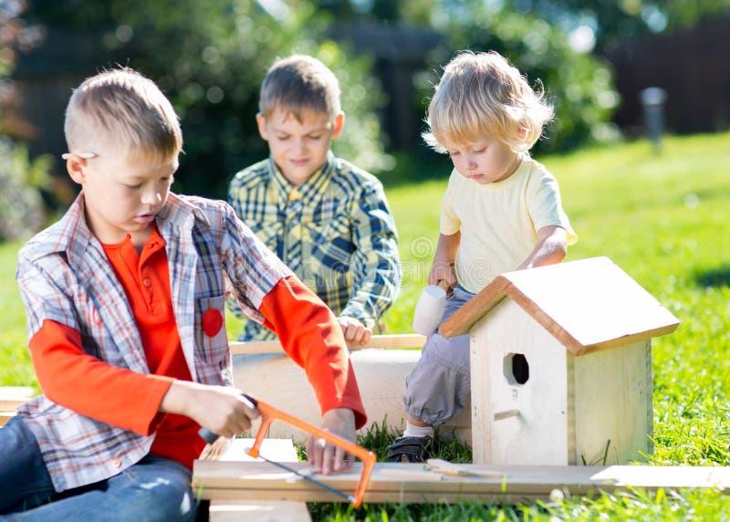 Glückliche Kinderbrüder, die hölzernes Vogelhaus durch Hände machen lizenzfreies stockfoto