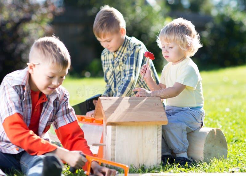 Glückliche Kinderjungenbrüder, die draußen basteln stockbilder