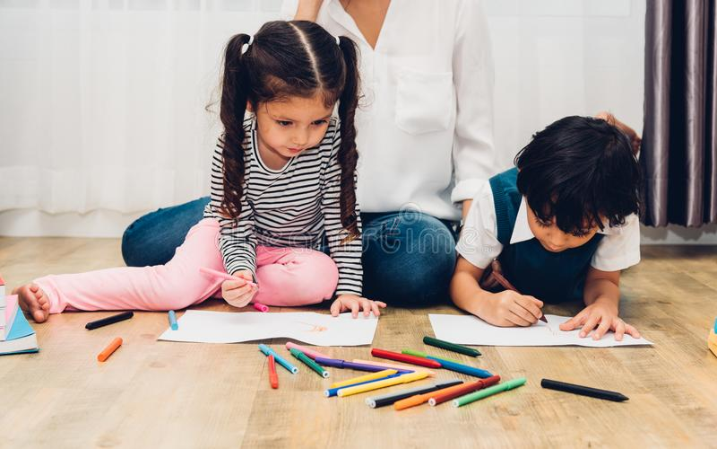 Glückliche Kinderkinderjungen- und -mädchenkindergartenzeichnung auf peper unterrichten stockfotografie