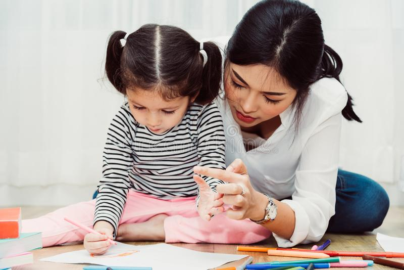 Glückliche Kinderkindermädchensohn-Kindergartenzeichnung auf peper Lehrerausbildung mit schöner Mutter lizenzfreies stockfoto