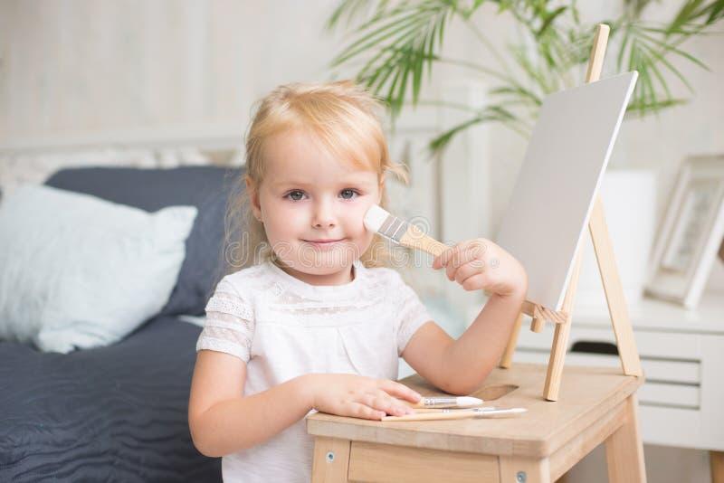 Glückliche Kindermalerei mit Gouache- und Aquarellfarben auf dem Gestell zuhause stockfotografie