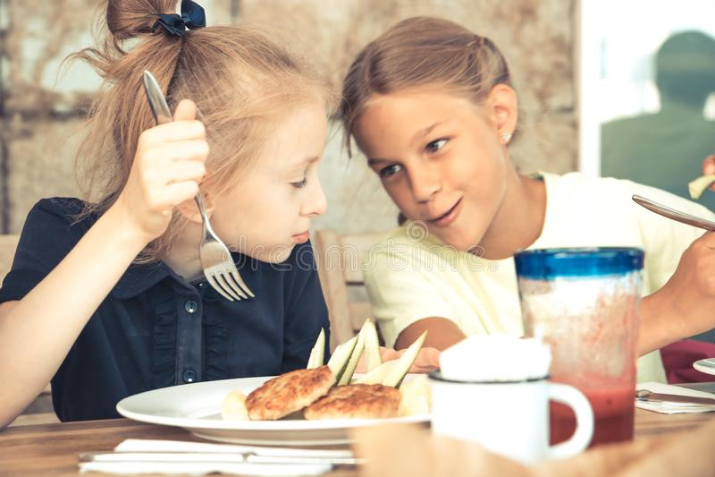Glückliche Kinderschwestermädchen, die eine Ruhezeit im Caférestaurant zusammen spricht Kindheitslebensstil haben stockfotografie