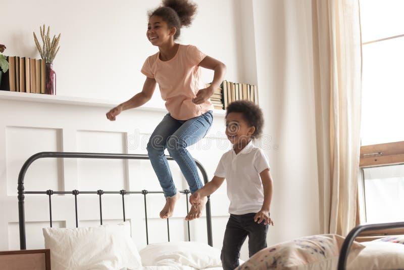 Glückliche kleine afrikanische Kinder Junge und Mädchen, die auf Bett springen stockfotografie