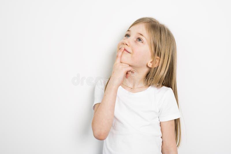Glückliche kleine fünf Jahre alte Mädchen mit dem geraden Haar über weißem Hintergrund zu Hause lizenzfreie stockfotografie