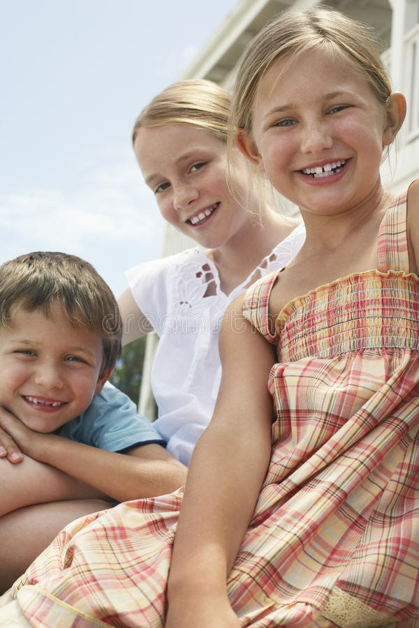 Glückliche kleine Geschwister, die zusammen sitzen lizenzfreies stockfoto