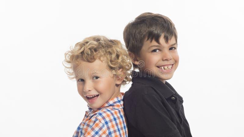 Glückliche kleine Jungen, die zurück zu Rückseite sitzen lizenzfreie stockfotos